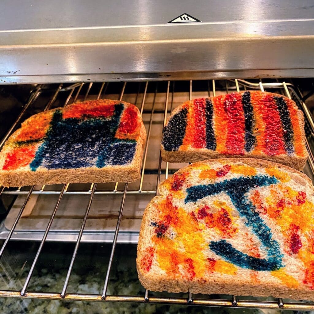 three pieces of painted toast in toaster oven