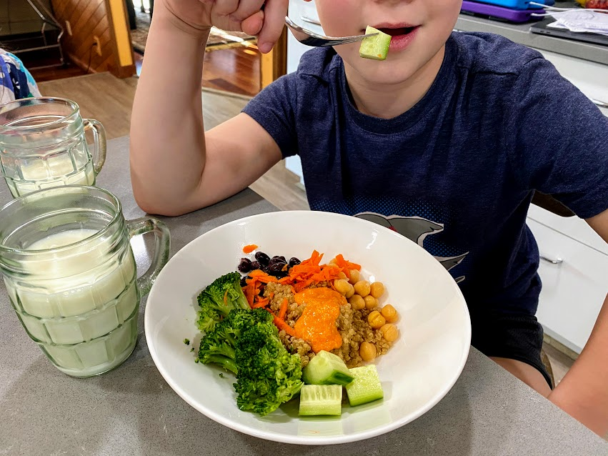 child eating romesco recipe with carrots, broccoli, cucumber, quinoa, chickpeas and cucumber, in white bowl