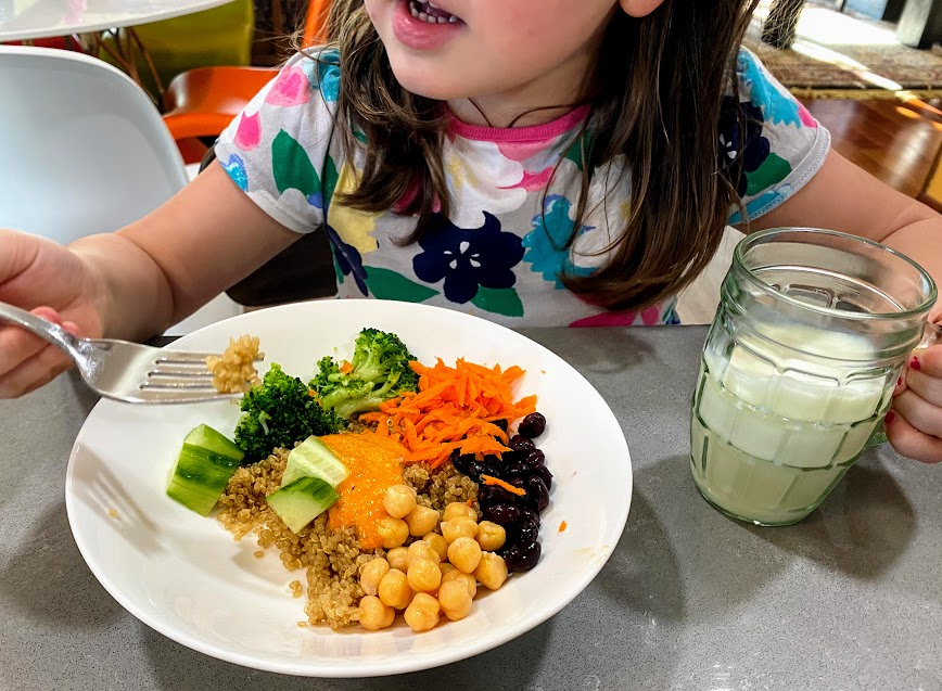 child eating romesco recipe with carrots, chickpeas, broccoli, quinoa, cucumber and black beans in a white bowl