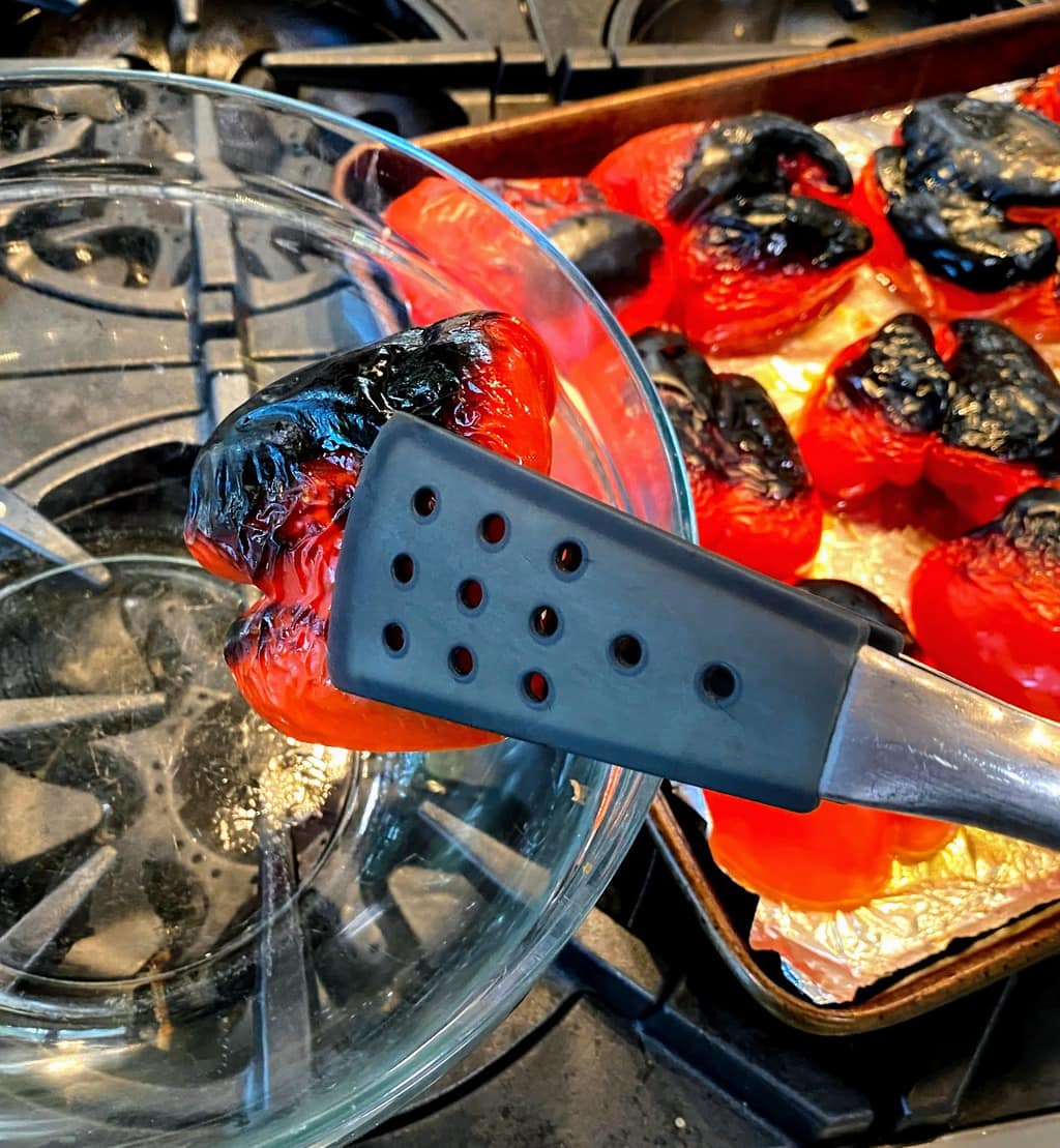 tongs moving roasted peppers from baking sheet to large glass bowl