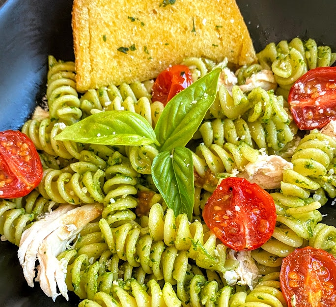 black square plate with chicken pesto pasta and roasted tomatoes