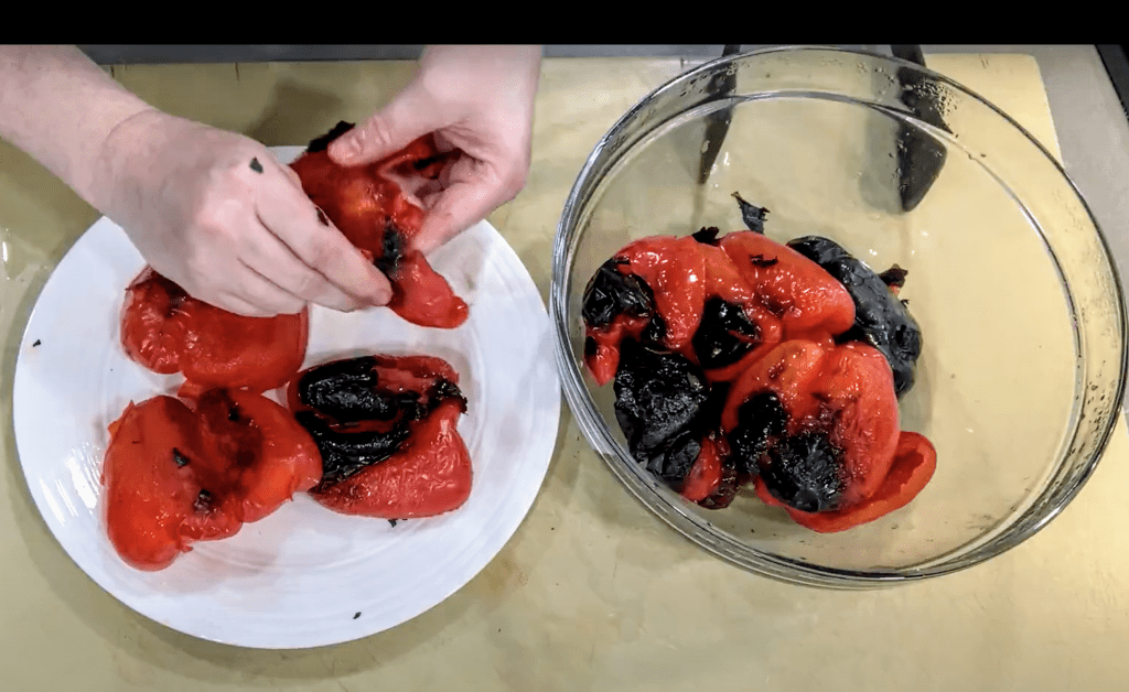 hands peeling skin off of roasted peppers on white plate