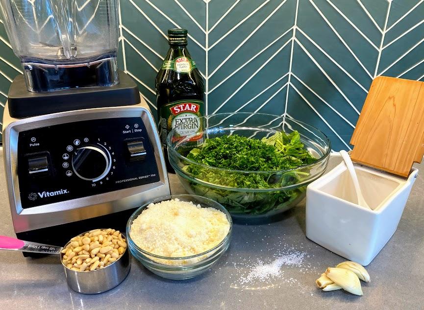 pesto ingredients on counter (vitamix, pine nuts, parmesan cheese, greens, garlic and salt)