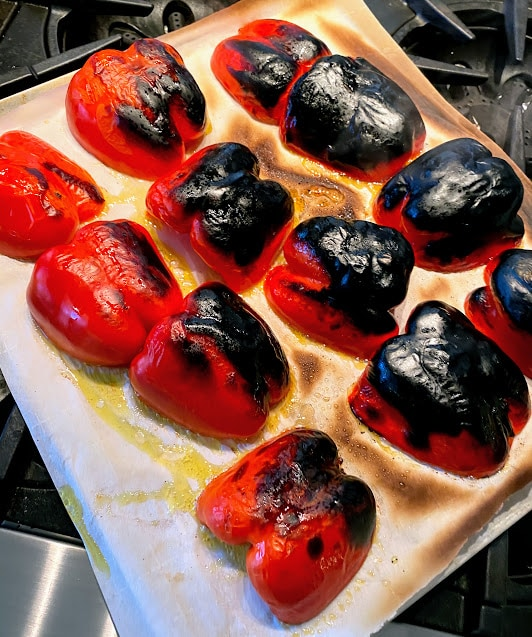 six, halved, roasted bell peppers out of the oven on a baking sheet