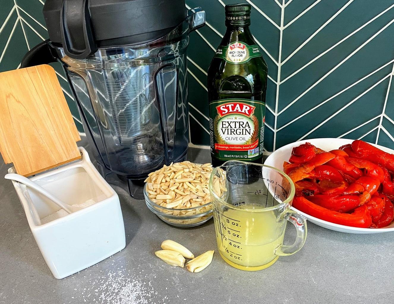 romesco sauce ingredients on counter: roasted peppers, lemon juice, garlic cloves, almonds, olive oil, salt and blender