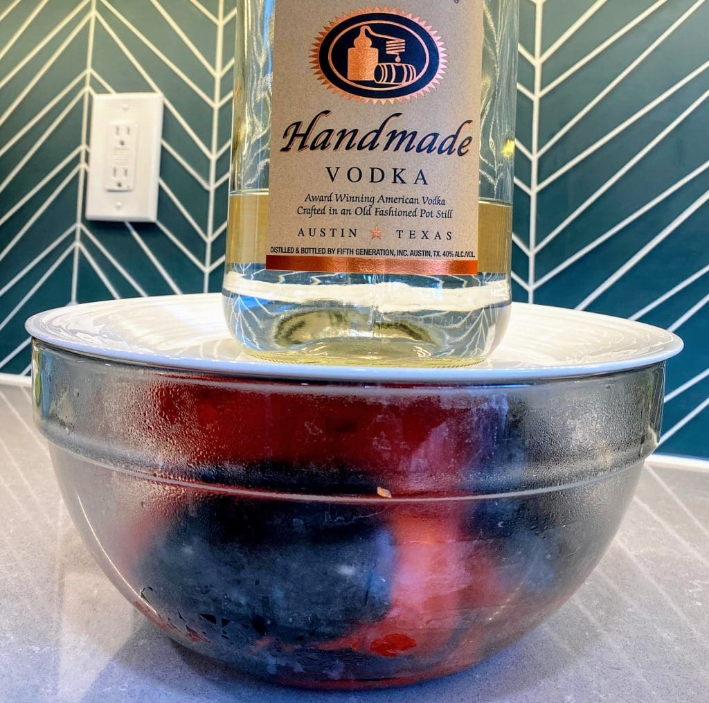 large glass bowl of roasted peppers steaming with white plate and and heavy liquor bottle holding a seal