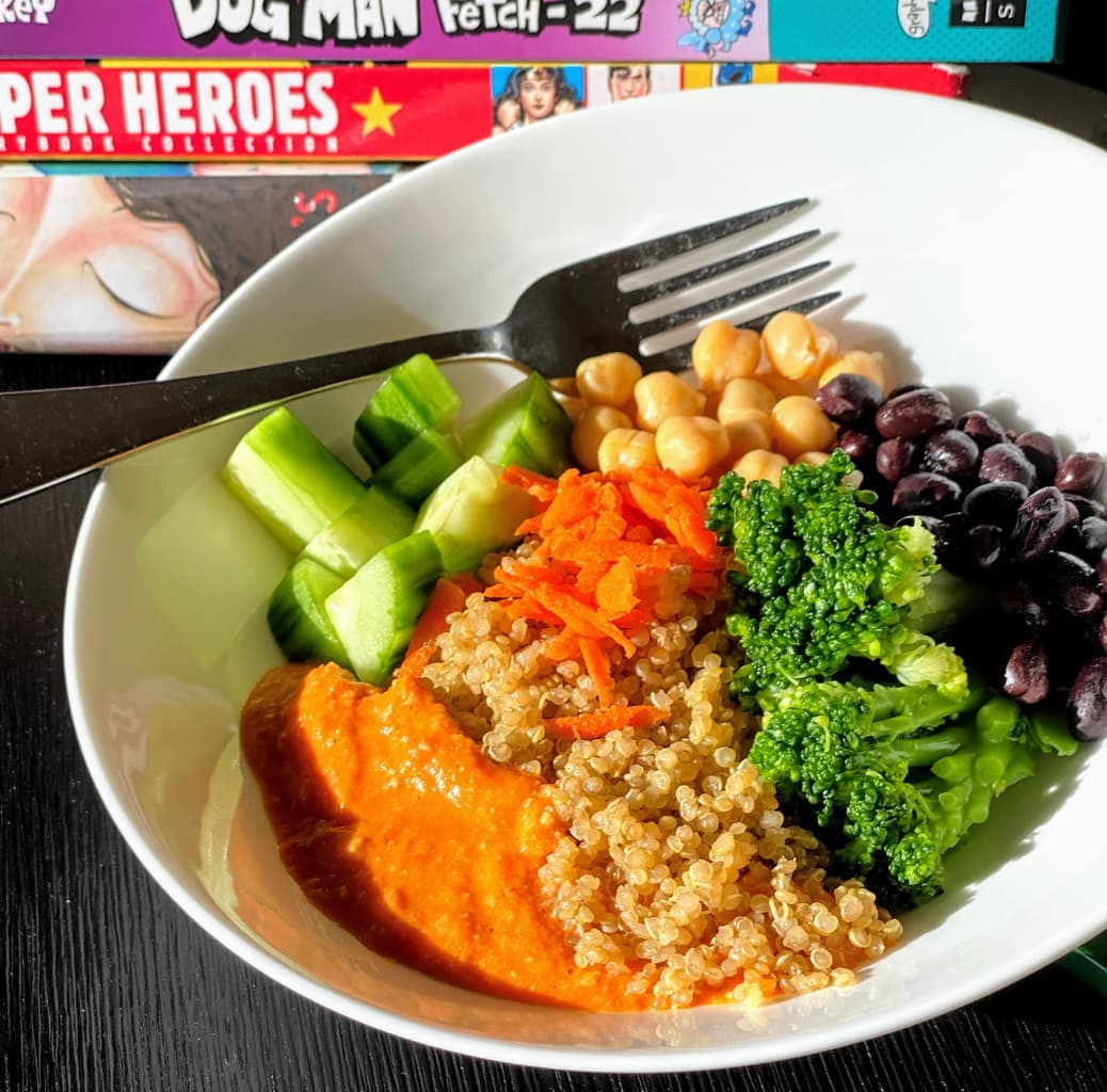 kids book next to white plate filled with veggies, romesco sauce and quinoa