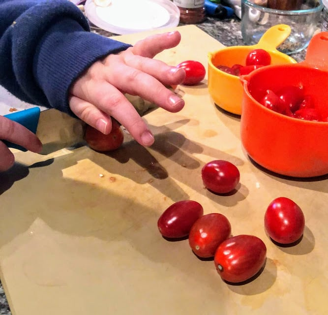 Child's hand cutting tomatoes on manila colored cutting board with blue kid's knife