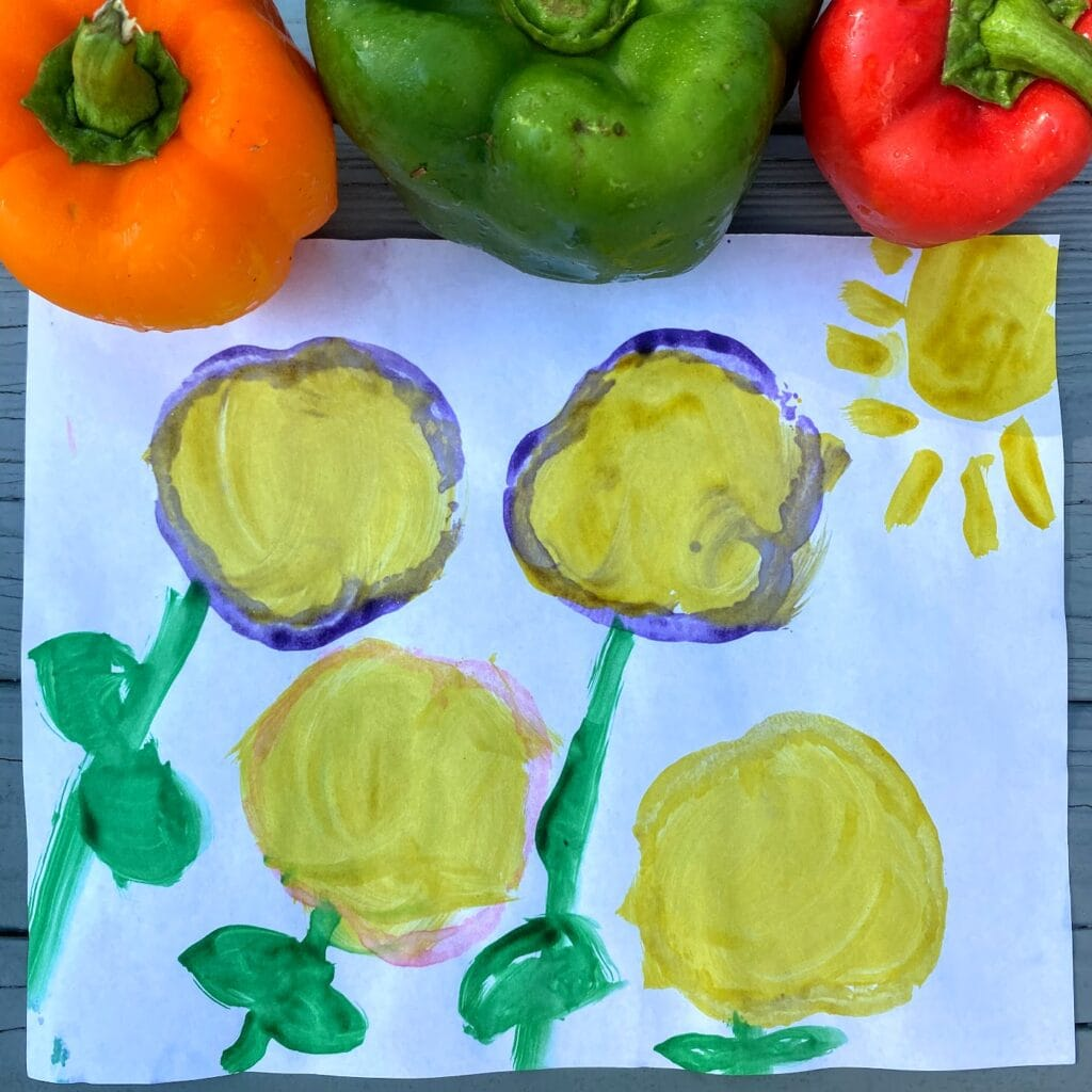 Four colorful flowers made from bell pepper stamps