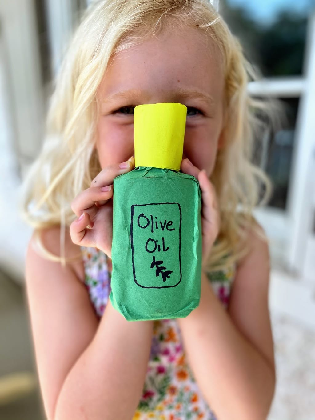 "Child holding completed olive oil bottle craft with ""Olive Oil"" logo"
