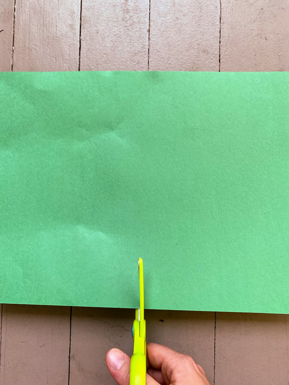 child cutting green paper in half
