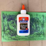 laying empty glue bottle onto green paper covered with glue