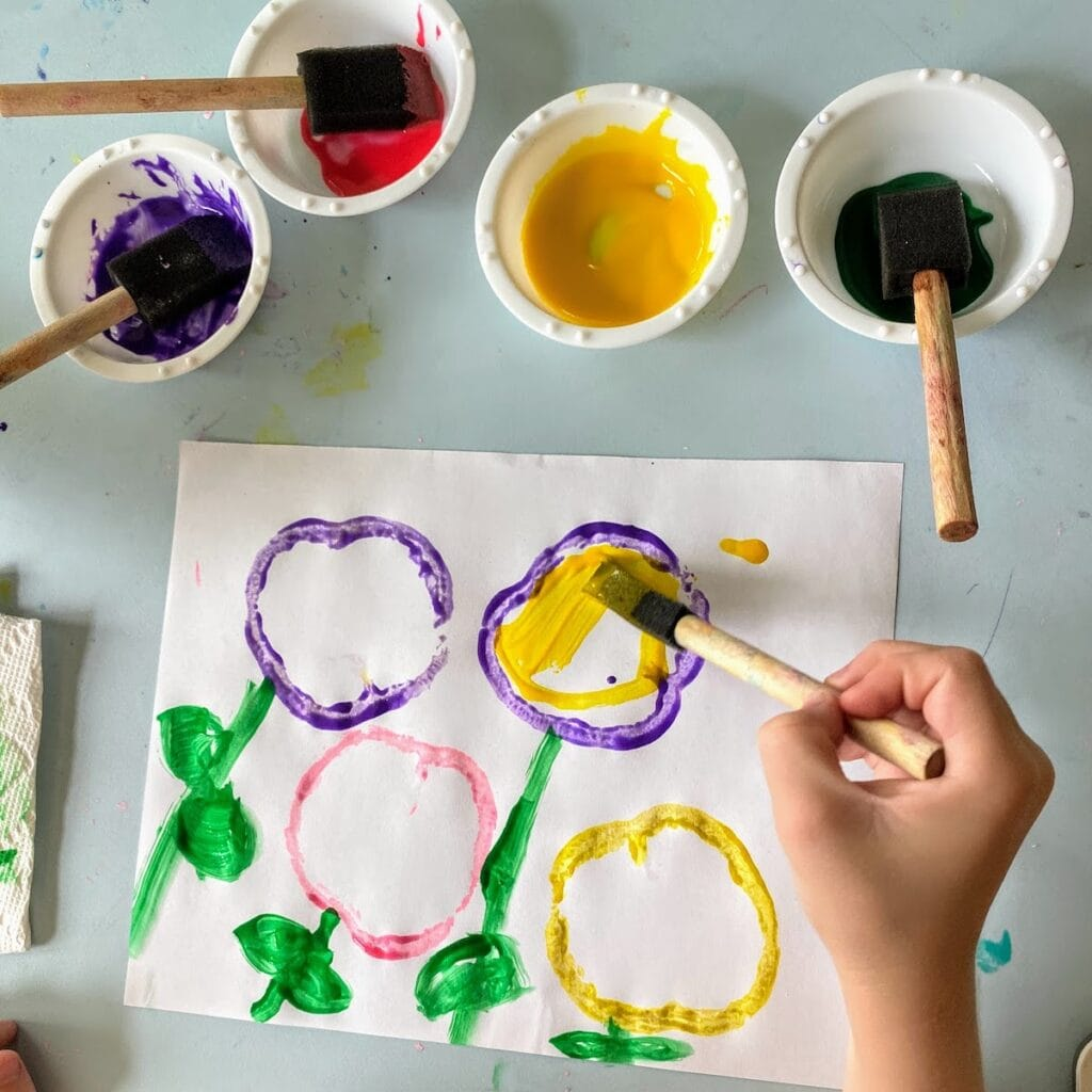 child coloring yellow flour made from bell pepper stamps