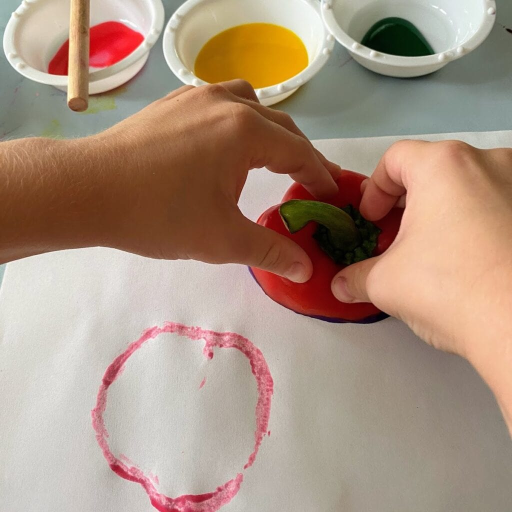 stamping a painted bell pepper top onto paper