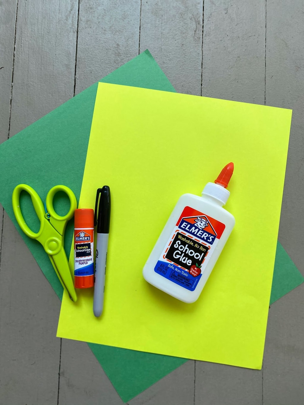 scissors, glue, black marker and yellow and green paper for olive oil bottle craft