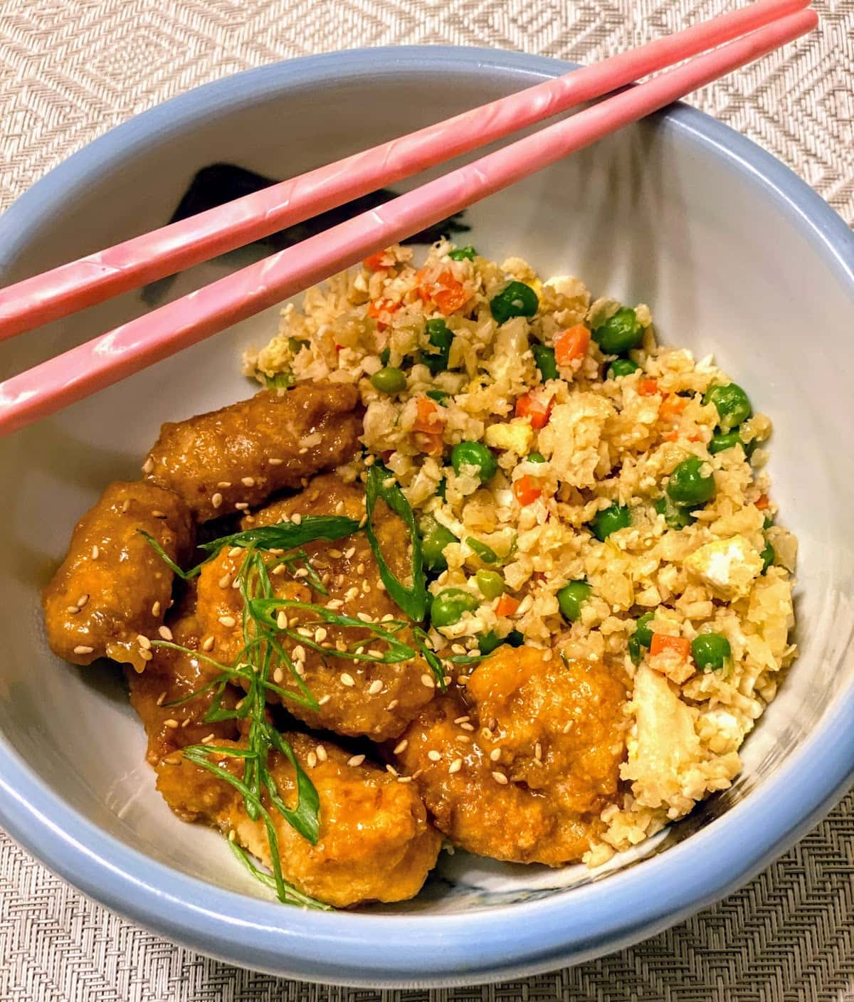 Cauliflower Egg Fried Rice with Orange Sesame Chicken in a Bowl with Pink Chopsticks