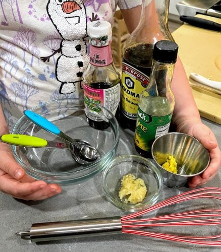 child holding ingredients for cauliflower rice sauce, plus measuring devices, whisk and bowl