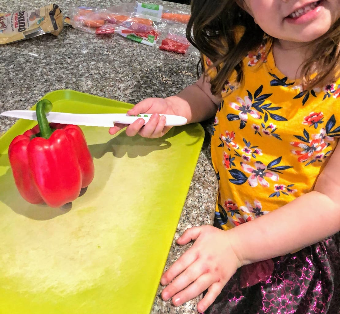 child about to cut the top off a red bell pepper