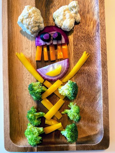 fun monster made out of veggies on a wooden tray