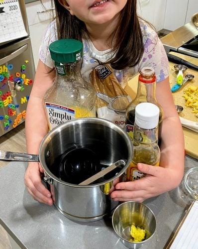 child holding ingredients for Orange Sesame Chicken Sauce