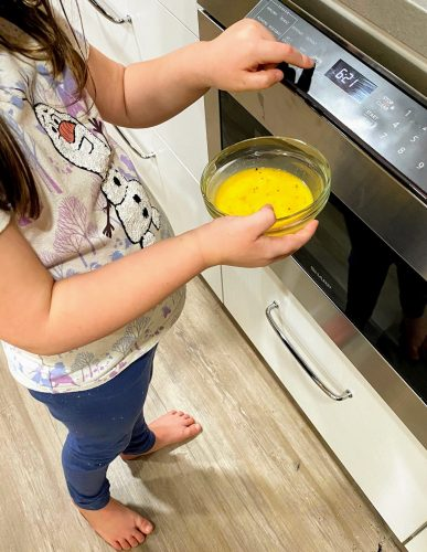 child putting whisked eggs into microwave