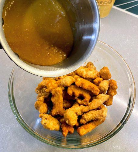 Pouring orange sesame sauce on chicken