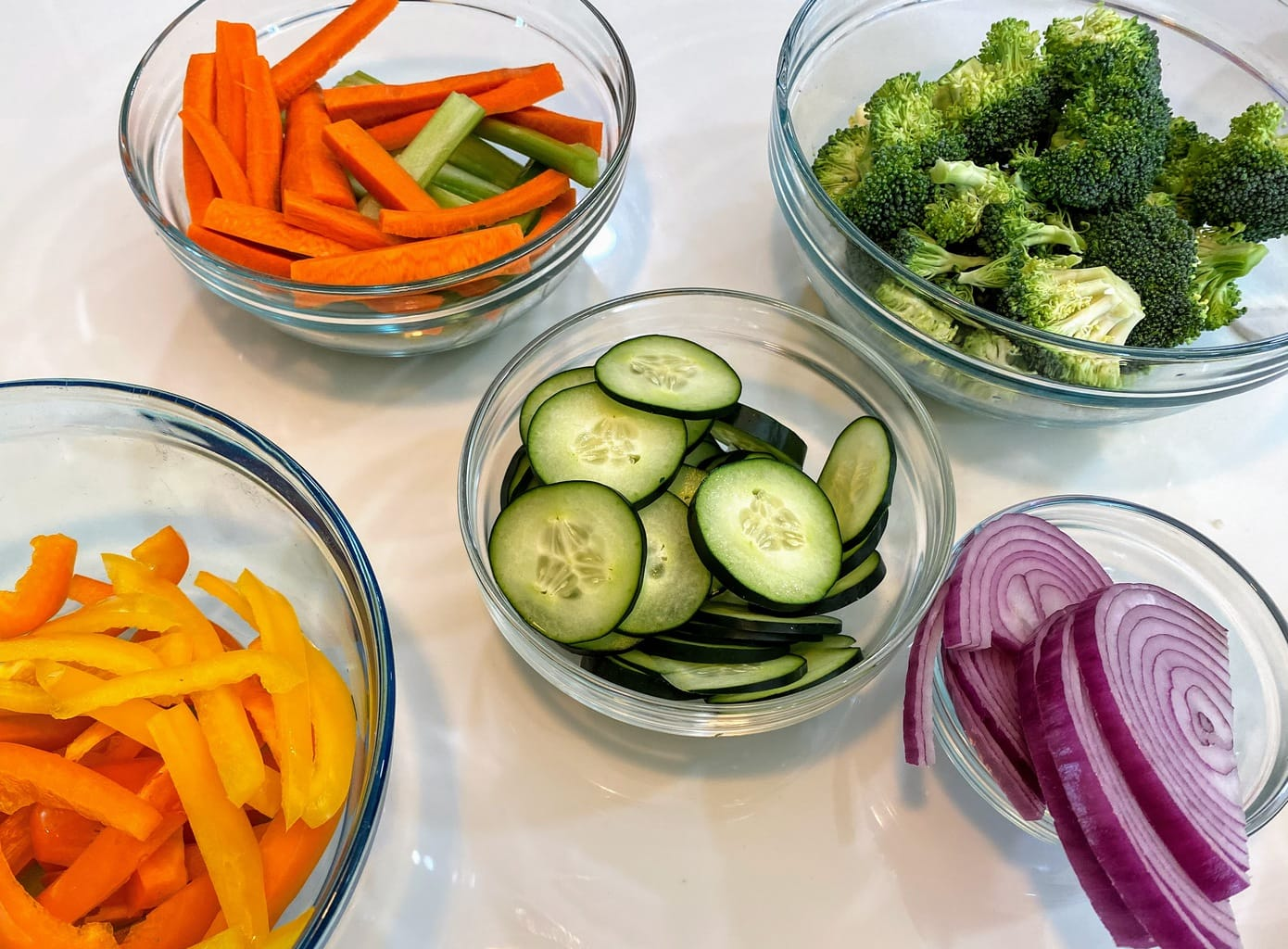 clear glass bowls of different, cut veggies on a white table