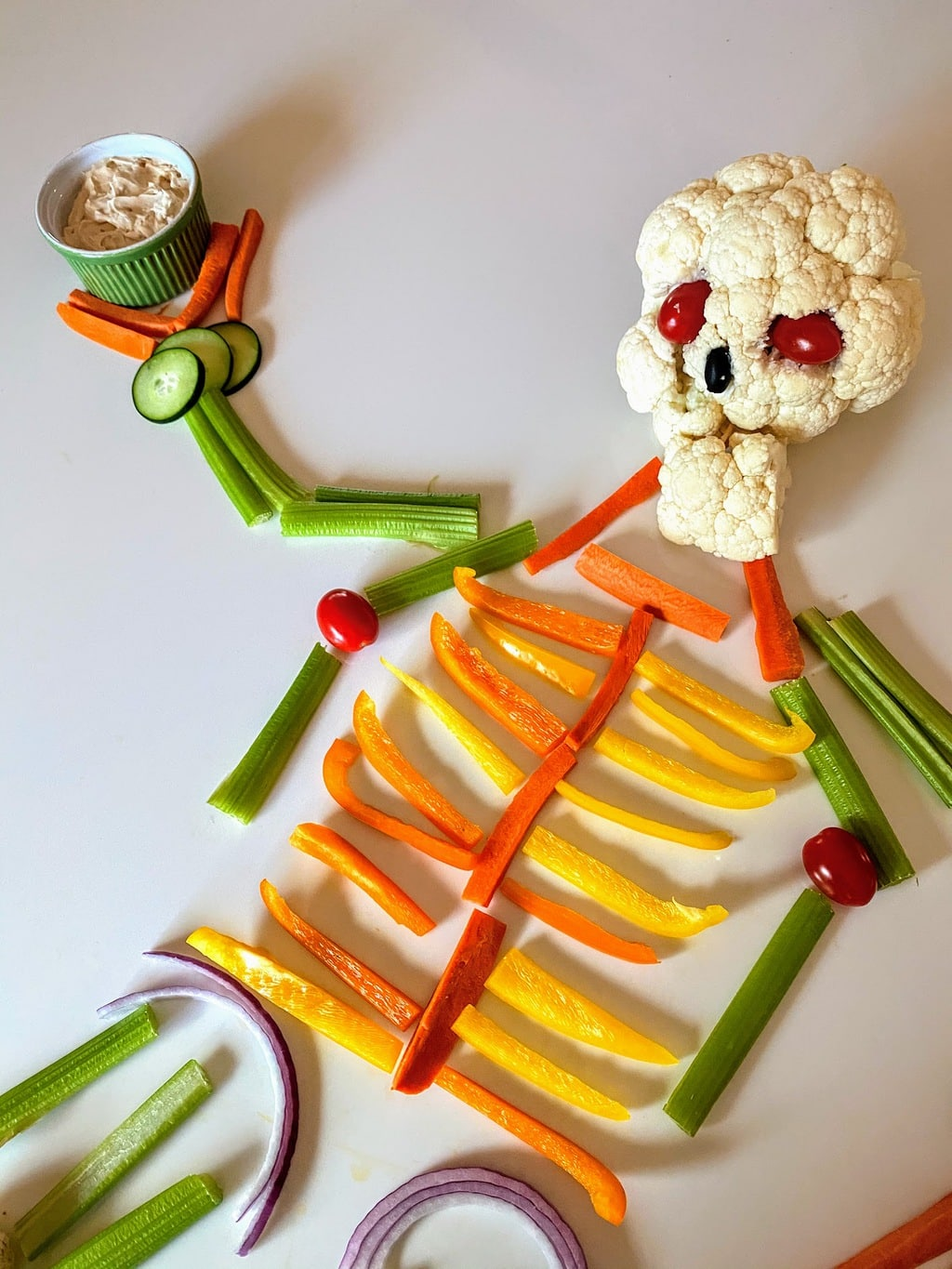 skeleton made of vegetables, with a cauliflower skull, holding a bowl of dip