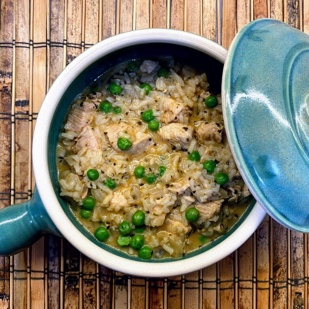 chicken, rice and peas in small blue crockpot with lid on side