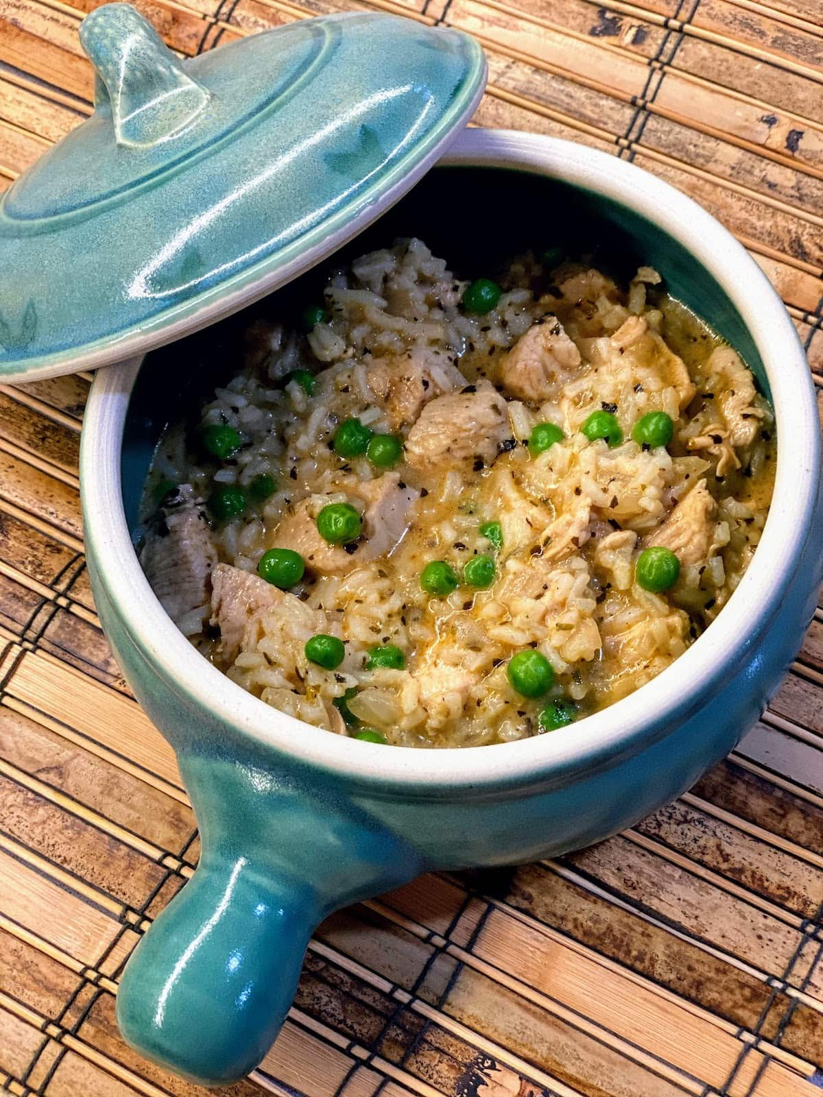 small blue crockpot filled with chicken, rice and peas