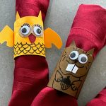 two DIY critter napkin rings on red napkins
