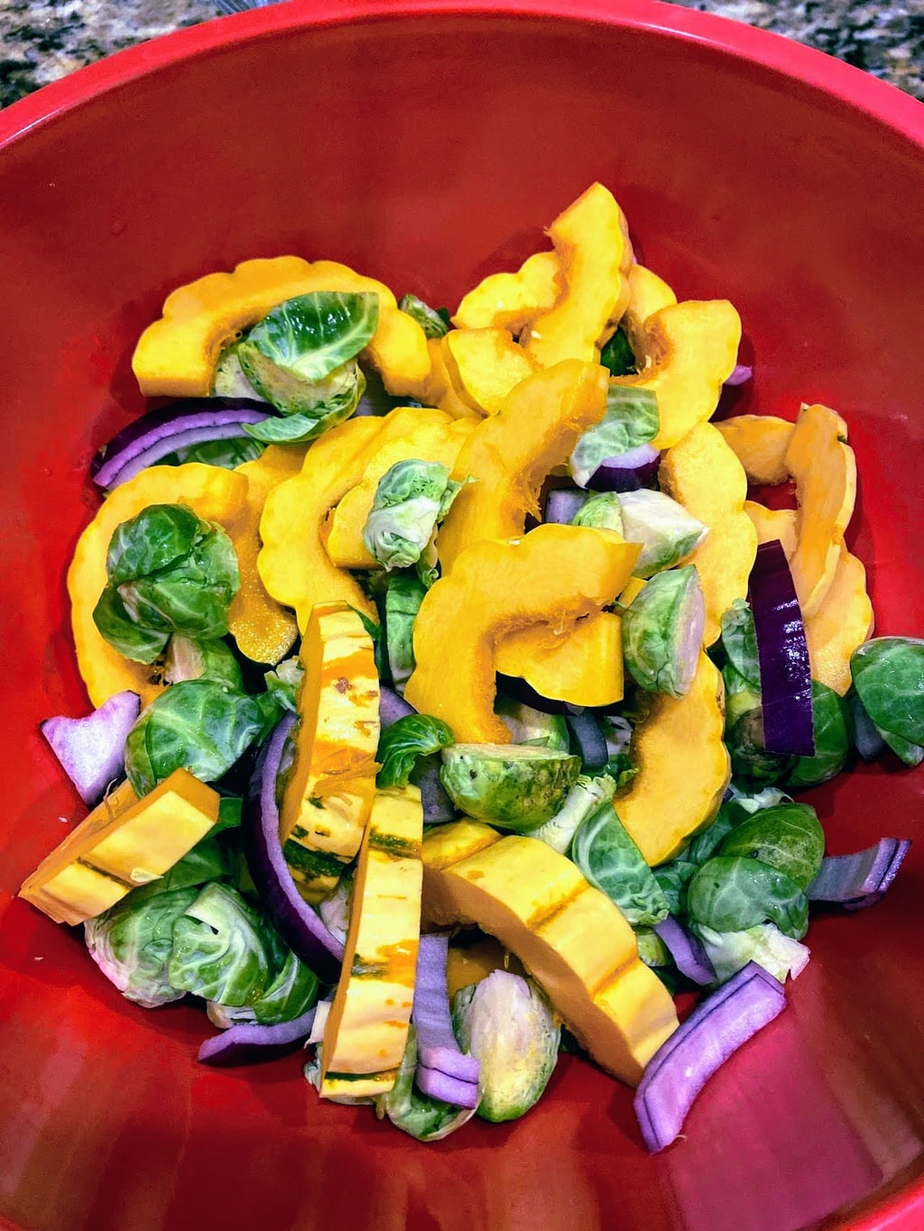 delicata squash slices, cut brussel sprouts, and sliced onion in a red bowl