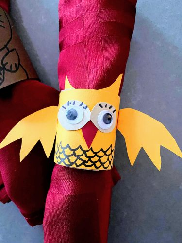 DIY yellow owl napkin ring holding red napkin