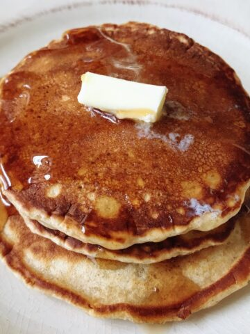 three stacked pancakes with butter and syrup