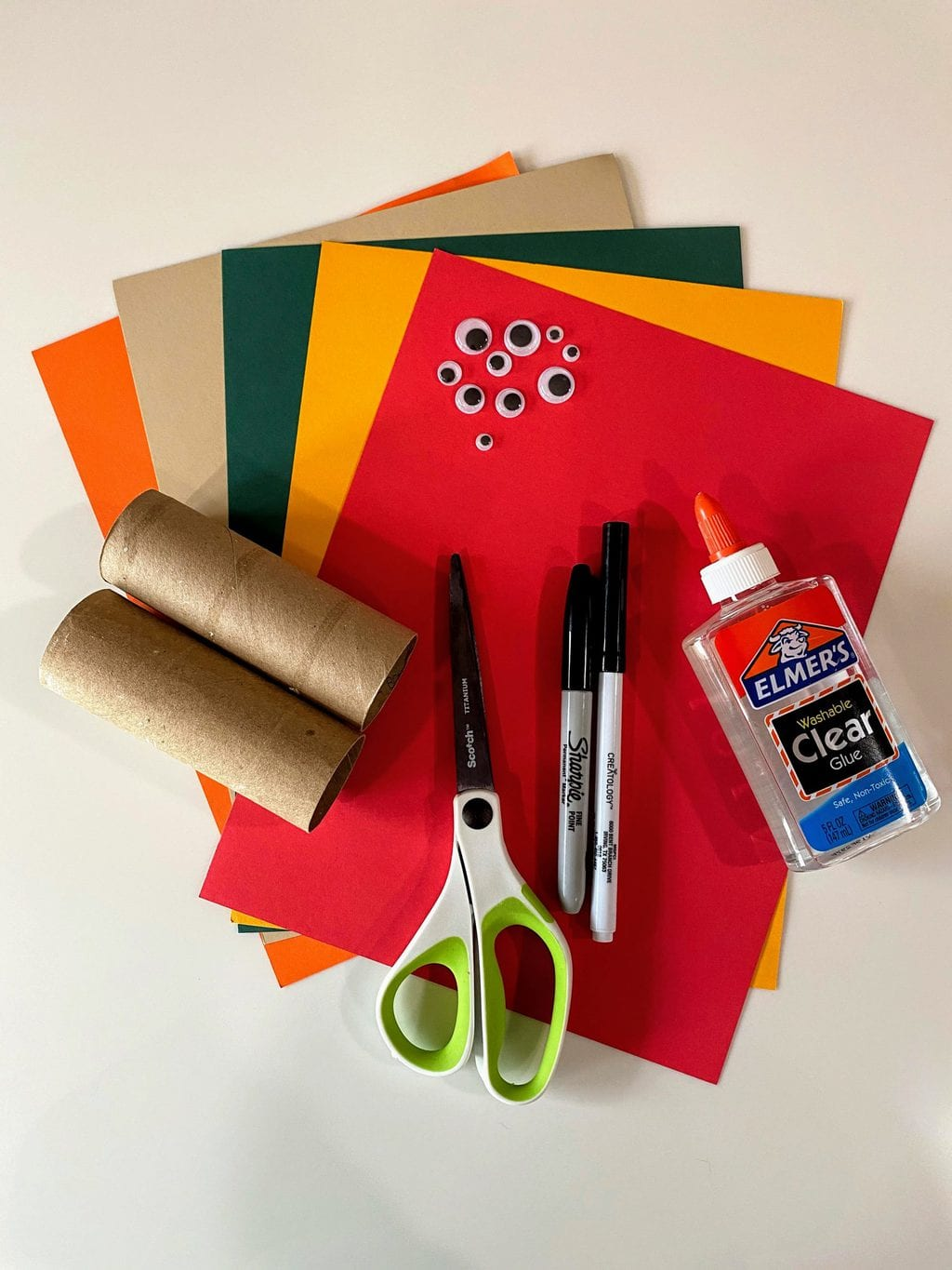 craft supplies for DIY napkin rings; colored paper, goggley eyes,  toilet paper rolls, pens, scissors and glue