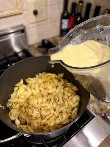 pouring vegan cheese onto shell pasta for tasty vegan mac and cheese