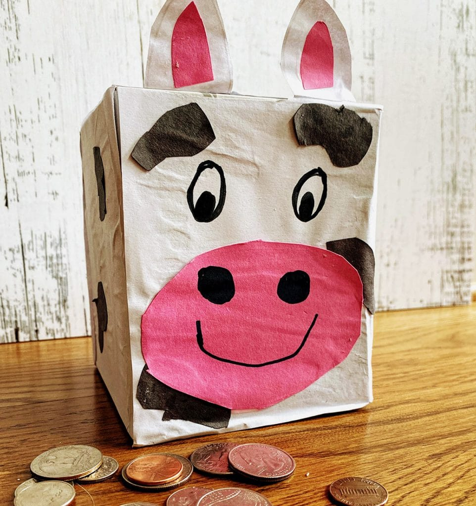 piggy bank in shape of cow surrounded by coins