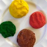 yellow, brown, red and green play dough on a plate