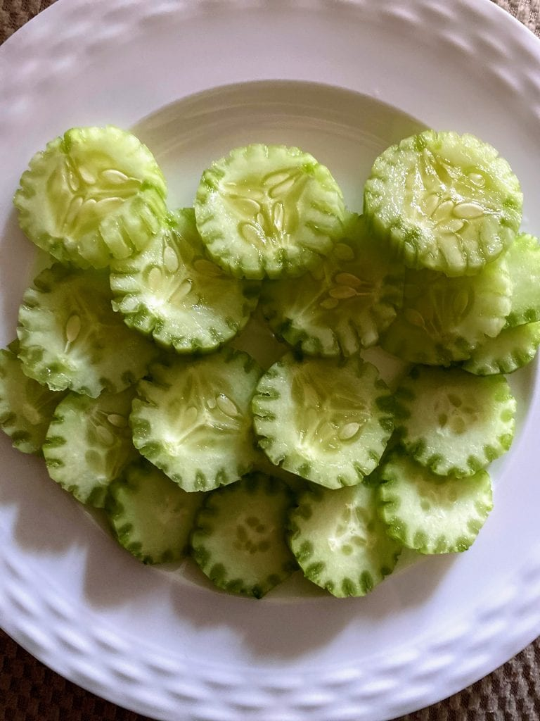 sliced and scored cucumbers on white plate