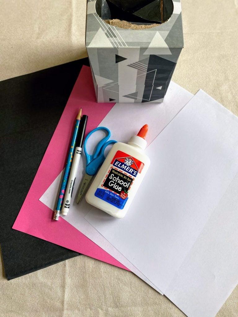 paper, tissue box, scissors, and glue