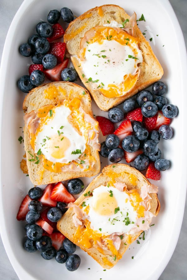 three pieces of toast with fried egg in the middle and surrounded by berries
