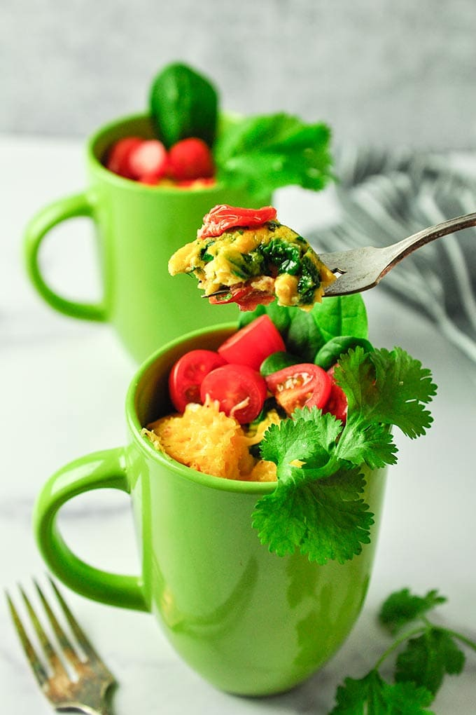omelette in a green mug, topped with veggies