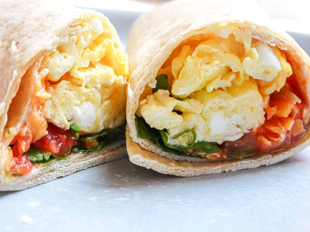 breakfast burrito cut in half with tomatoes and greens