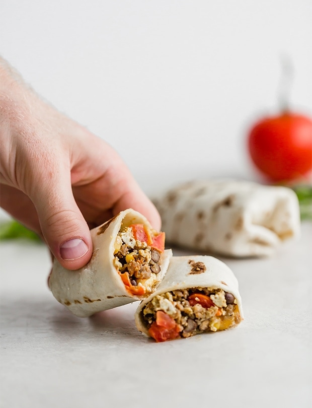 sausage and egg burrito cut in half and filled with veggies