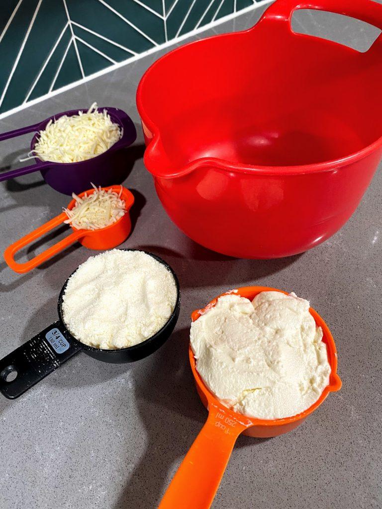 parmesan, mozzarella and ricotta in measuring cups