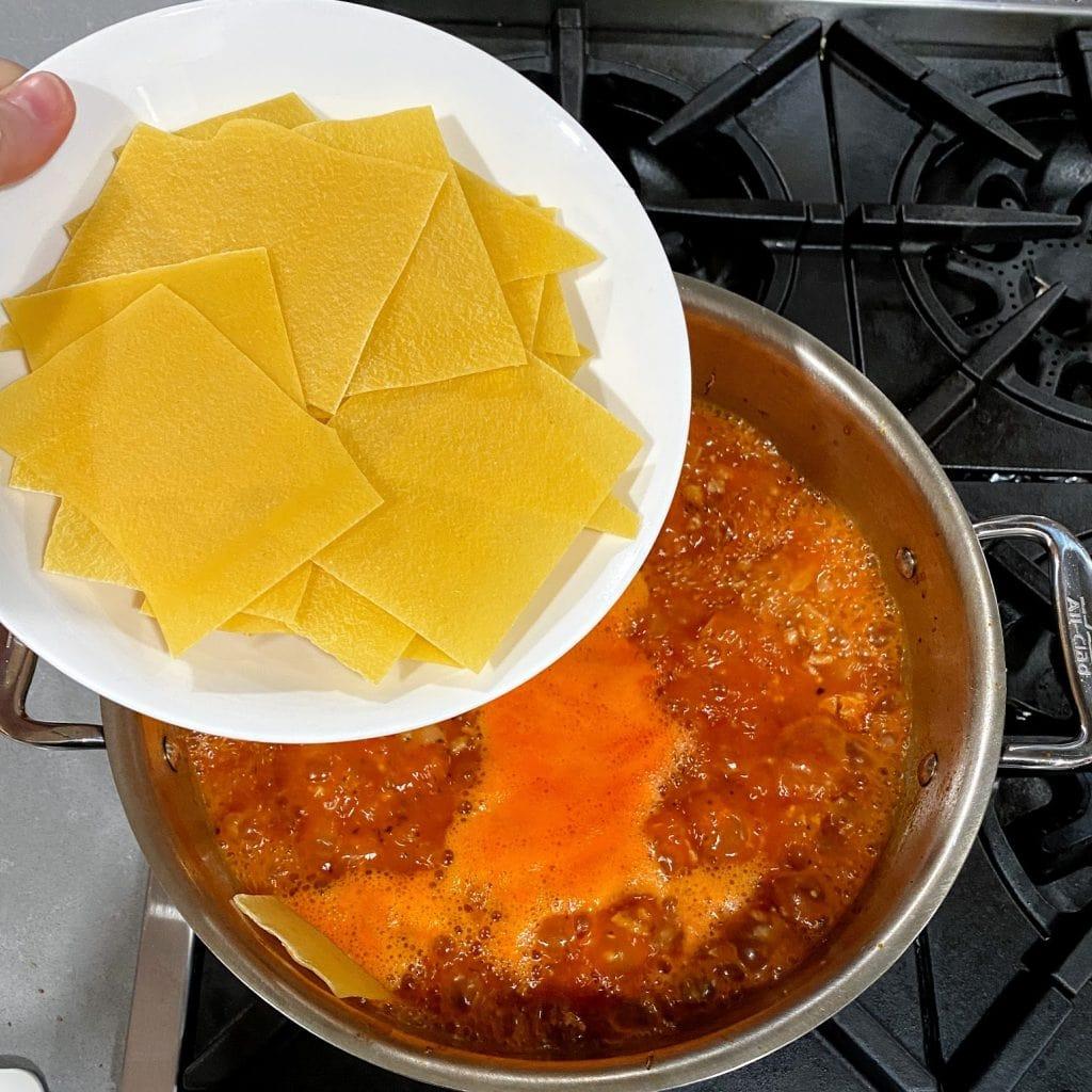 adding lasagna noodles to pot of lasagna soup
