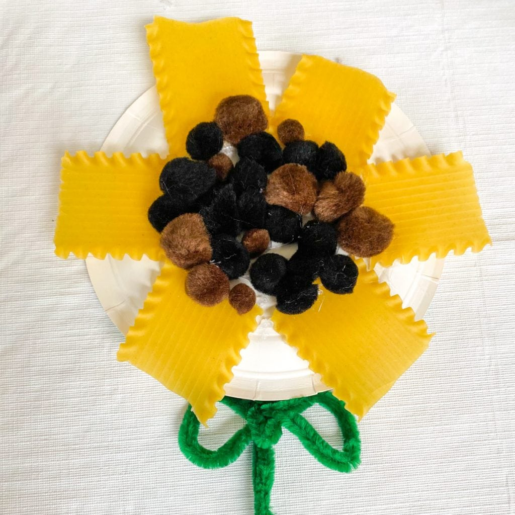 Paper plate sunflower made with lasagna noodles and pompoms