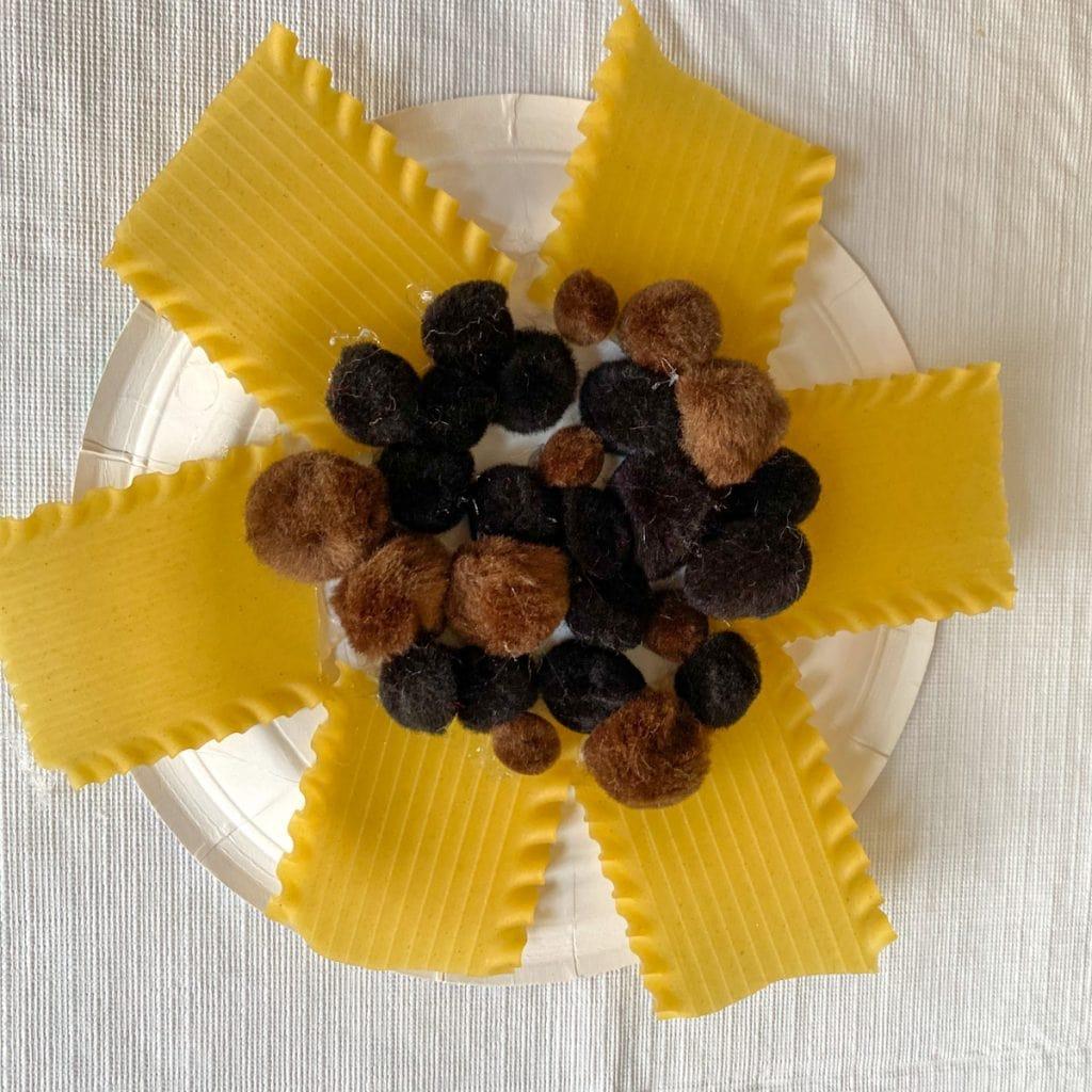 several black and brown pompoms glued onto center of sunflower