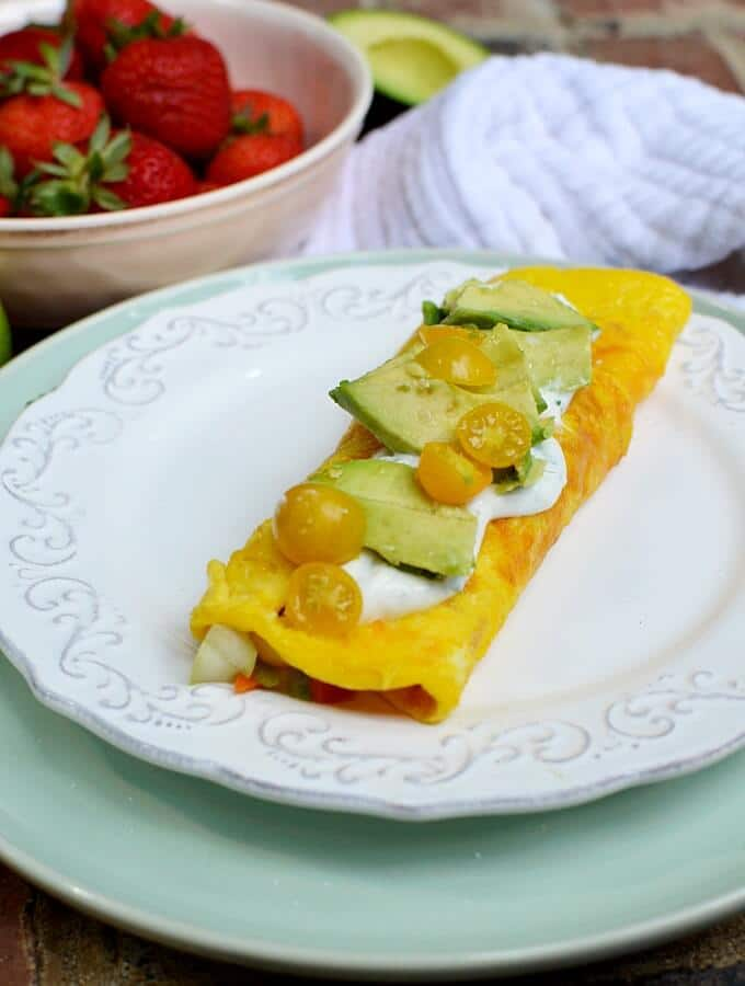 omelette with yellow tomatoes and avocado on a whit plate