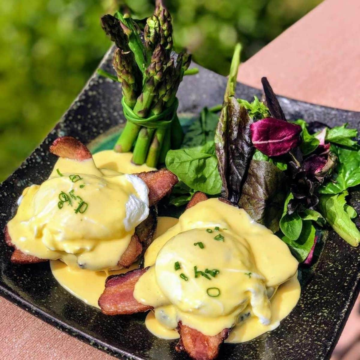 eggs benedict with bacon, asparagus, and mixed greens